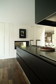 Gorgeous contemporary kitchen. Black cabinets, dark wood flooring and cool square faucets.