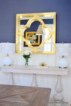 A simple white lamp with a geometric shade adds an unexpected design element.  Adding a pair of lamps to a console table adds symmetry.  And, the lighting from the lamps add a warmer touch and bring light throughout the space. Sponsored by Happy by Design