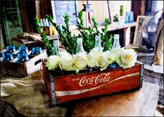 A unique a delightful vintage gift centerpiece. An authentic vintage Coca-Cola wooden crate, complete with glass Coca-Cola bottle, white roses and greenery. You may add candles for the Coke bottles fo Christmas Table Centerpieces, Centerpiece Decorations, Christmas Decorations, Coke Crate Ideas, Coca Cola Kitchen, Unique Gifts For Mom, Always Coca Cola, Coca Cola Bottles, Vintage Bottles