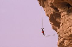 A tribesman climbing a cliff with the help of a rope, Ireli, Africa. - stock photo