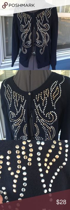 """TOP KNITS Navy Blue Studded Cardigan Sweater Stunning! TOP KNITS Navy Blue Studded Cardigan Sweater.   Gold & silver studded front adornment.  Long sleeves.  Button down front. Navy blue cotton/nylon/rayon blend fiber knit.  Shoulder width 16"""".  Pit-to-pit 19"""". Length 22-1/2"""" (shoulder to hem).   Excellent condition. Top Knits Sweaters Cardigans"""