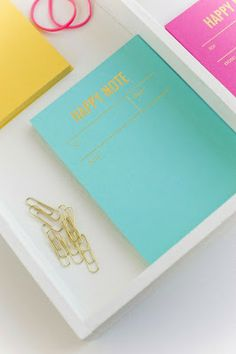 happy note book in blue, yellow and pink with gold letters