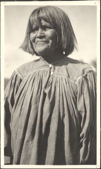 Nat-kit-is-dell, a White Mountain Apache woman, posing outside in a cotton dress. Culture/People:White Mountain Apache Date created:September 30, 1919