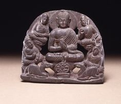 A small openwork panel depicting the First Sermon of the Buddha. The seated Buddha is flanked by four listeners and below his throne the dharmacakra and a pair of deer.