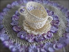Crochet cups/saucers sitting on the crochet pansy doilies.