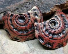 Polymer clay drop beads with natural textures in shades of rusty red and black. Overtones of metallic golden bronze.