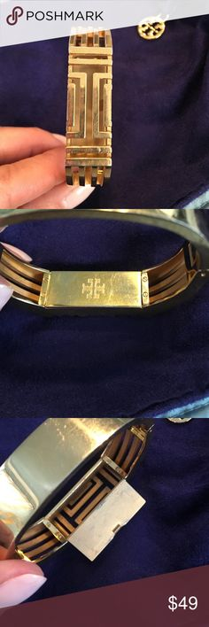 Tory burch fit bit bracelet Authentic Tory burch metal fit bit bracelet.  Some scratches and some metal worn, but still looks very nice. Latch is a little warped and opens easily if not being worn. Fit bit stays in by itself. Tory Burch Jewelry Bracelets