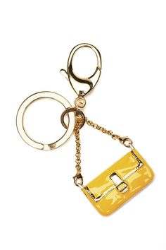 Charm Baguette in metal with gold finishings, and yellow-enameled chain and charm.