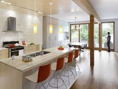 modern open-plan kitchen with quartz countertops, maple cabinets, and red bar stools Home, Modern House, Open Plan Kitchen, New Kitchen, Energy Efficient Homes, Sustainable Home, Maple Cabinets, Modern Kitchen Open Plan, Kitchen Design