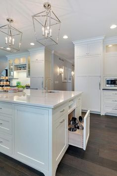 Gorgeous kitchen island sat upon stained oak hardwood floors features white shaker cabinets topped with a white marble countertop fitted with a curved prep sink and polished nickel faucet illuminated by two 4 light Darlana lanterns and recessed lighting. by adrian