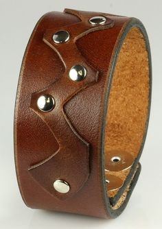 """This leather bracelet has a width of 1.25"""" and features a zig-zag strip of thin…"""