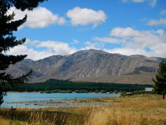 Lake Tekapo, New Zealand.     A mirror lake reflecting the gorgeous sky, a backdrop of majestic mountains, the Church of the Good Shepard surounded by golden wheat grass.      Travel, motivation, inspiration.