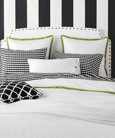 Bright green trim on a black and white bed set adds a refreshing pop of color.