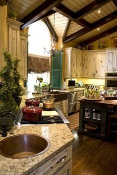 Modern French country kitchen...exposed beams, distressed wood cabinets, stucco walls...<3