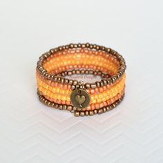 This memory wire bracelet is made with seed beads in graduated colors from bronze to burnt orange to pale orange. The beads are strung on antique