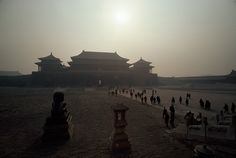 The huge Gate of Heavenly Peace, the main entrance to the Forbidden City in Beijing, looms in the dusty early morning haze which partially obscures the sun. This view, taken from Tiananmen Square, shows the tiny figures of people walking along the main thoroughfare leading to the gate, 1978. Photograph by James P. Blair, National Geographic Creative