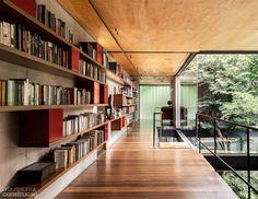 Aproveitando o corredor largo para dispor os livros. Detalhe todo especia para o teto revestido de madeira, muito aconchegante. Projeto do arquiteto Fernando Viegas.