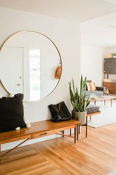 The Airy + Open Home of Graphic Designer.  Lovely large circle mirror with unique bench at entryway
