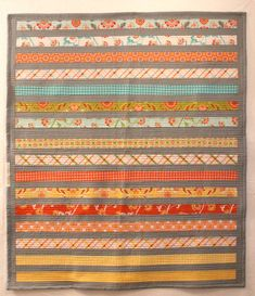 Get cozy this fall or winter with your little boy or girl in this colorful, warm, modern quilt handmade just for you. Also great as as a lap blanket! Measuring 44 x 50 inches (111 x 127 cm), this quilt will fit perfectly in a toddler bed or folded and ready to use in the living room. Designed to look good from any angle, with the stripey side up the soft flannel side will certainly soothe your kiddo to sleep.    Brightly colored strips of 2 inch-wide fabric in coral, yellow, green, blue and…