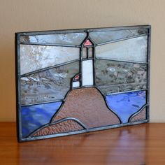 Lighthouse on the rocks. Designed and made by Radiance Stained Glass.