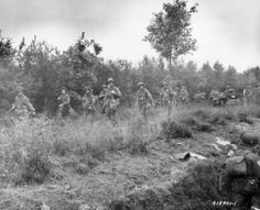 Some 101st paratroopers walking by during Market Garden. If u look closely at the man standing to the right of the paratrooper with the first aid pouch on his helmet he is wearing a rigger pouch