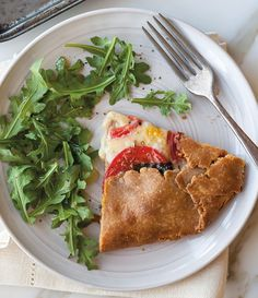 Heirloom Tomato, Mozzarella and Basil Galette | A whole wheat + cornmeal crust is the perfect base for a freeform tart packed with summer's best flavors: ripe tomatoes, creamy mozzarella and fresh basil.
