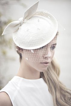 Our Adele hat is a small saucer shape hatwhich has been hand formed.  Made  from off white velour felt and finished with a small veil.  Item details     * The hat attaches with a headband.     * Made to order.     * Choice of veils available.