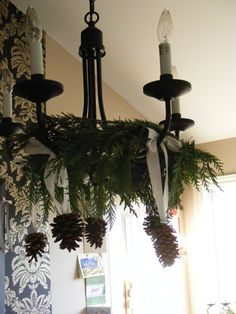 fresh greenery wreath around chandelier with ribbons and pinecones - doing it this year - think i'm going with fresh greenery all around