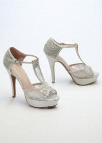 "Hot and elegant, these high heel sandals will take your special occasion outfit to the next level! Glitter and lace adorned t-strap is ultra-feminine and chic. 4 1/4"" heel. Fully lined. Imported. Buckle closure."