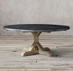 RH's Railroad Tie Round Dining Table:Rough-hewn timbers with the character and heft of salvaged railroad ties form the base of our dining table. A classic trestle style hearkens back to its 17th-century origins, while the top is hand wrapped in brass with the deep-grey finish of aged zinc.