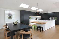 aménagement cuisine blanche, noire et bois avec ilot central avec coin-repas et salle à manger