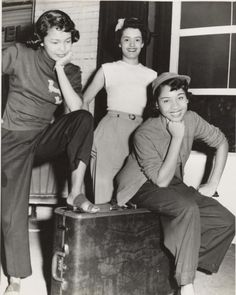 Three woman pose around a suitcase in Pittsburgh, Pennsylvania, 1950s.
