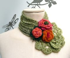 This little and soft scarflette, made of a grass green yarn, is perfect to keep your neck warm while looking stylish... a little posy of bright wild flowers decorates this unique creation... a bunch of grass blades which ends with two simple crocheted laces.