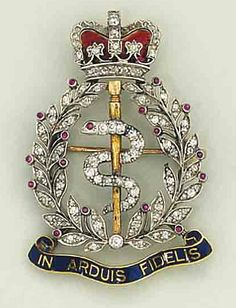 A diamond, ruby and enamel regimental badge brooch   For the Royal Army Medical Corps, the central single-cut diamond entwined serpent within a single-cut diamond wreath with cabochon ruby accents, to a single-cut diamond and enamel crown surmount and blue enamel wreath base with the legend IN ARDIUS FIDELIS