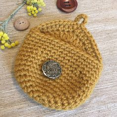 A simple little crocheted purse made in one piece– starting from the bottom up, in a spiral. The flap is then worked flat without breaking off the yarn and includes a button loop.