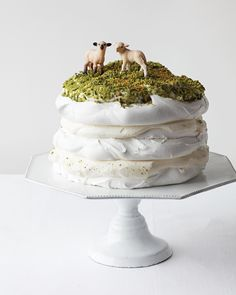 """An airy white pavlova layered with whipped cream is a dream on its own— no frosting required. We added a """"meadow"""" of pistachios and fennel blossoms and cute little lambs, for good measure."""