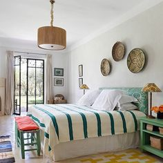 In another bedroom, a rug - a gift from a friend - brightens the scheme.  Trudi created a unifying element by using raffia ceiling lights from Henry Cath in all the bedrooms.