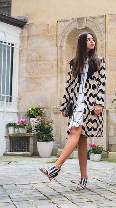 Amanda Cassou, sócia do Gallerist, veste sobretudo gráfico preto GIG, branco e marrom, vestido quadriculado preto e branco, sandália listras preta e branca, bolsa preta Les Petits Joueurs, street style, paris fashion week.
