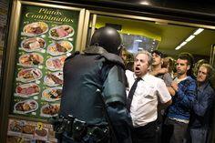 El dueño de un restaurante intenta proteger a los manifestantes que se encuentran dentro de su establecimiento.  DANIEL OCHOA DE OLZA (AP)