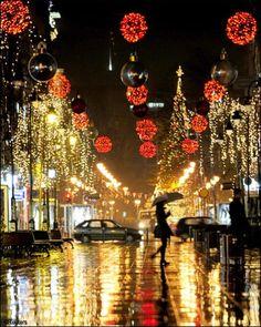 A woman walks near trees illuminated with Christmas lights in Skopje, Macedonia