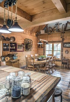The dining room in this Hochstetler Log Home showcases exposed beams and rustic decor. #loghomes #logcabins #exposedbeams #loghome #logcabin