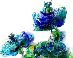 Splendido set di tre mano dipinto fiori Pavone può essere collocato in pentole, vasi, aggiunto al regime o semplicemente mettere in terra. Sono colorati, fiori di bottiglia di plastica upcycled simili Chihuly arte del vetro (ma non rompono!) Dopo il vostro giorno speciale, è possibile riutilizzare questi ripetutamente. Questo particolare fiore è composto da quattro bottiglie diverse. Posso aggiungere foglie a loro se ti piace.    Miei fiori sono costituiti da bottiglie di plastica che sono…