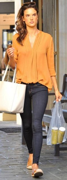 Who made Alessandra Ambrosio's blue skinny jeans, tote handbag, and tan pleated long sleeve top?