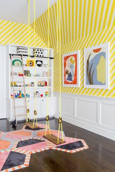 Two neon yellow swings with wooden seats hang in a playroom over multi-colored hex carpet tiles and in front of a white wainscot wall lined with yellow diagonal striped wallpaper. Source by decorpad ideas for teens Modern Playroom, Playroom Design, Kids Room Design, Yellow Playroom, Modern Kids Decor, Modern Kids Bedroom, Colorful Playroom, Bedroom Wall Ideas For Teens, Bright Bedroom Ideas