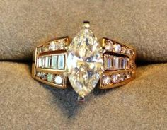 Marquise diamond ring with 26 fancy-cut side diamonds  in 14K yellow gold mount