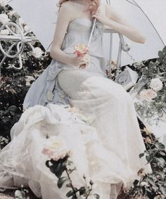 Editorial detail of Lily Cole on a bed of flowers in 'Pantomime' by Tim Walker for Vogue UK December 2004