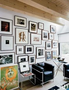 A home office's salon-style display includes images by Annie Leibovitz, Herb Ritts, Bruce Weber, Bill Brandt, Weegee, and others | archdigest.com