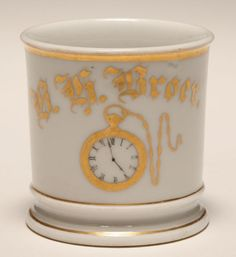 Occupational shaving mug, Horologist/Watchmaker. Gilt trim. Good condition, minor wear, tight line and firing flaw in handle.