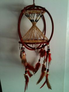 """2 7"""" rings with 3"""" dream catcher and 4"""" dream catcher at top and base. Red wrap. Beaded tee-pee in the center. Four hanging sterling silver feather pendants."""
