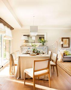 Comedor abierto al salón con sillas de madera tapizadas en blanco